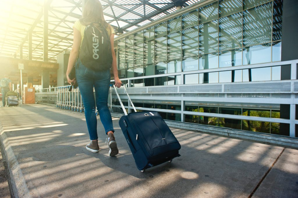 woman-walking-on-pathway-while-strolling-luggage-1008155-1024x681
